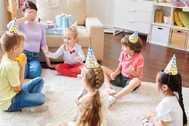 Junge frau, die ihre augen von hand bedeckt, während auf teppich vor gruppe von kleinen freundlichen kindern während des spiels im wohnzimmer sitzt