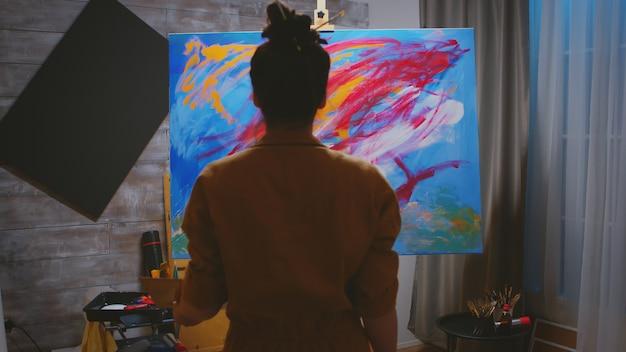 Junge frau, die ihre fantasie beim malen auf leinwand verwendet.