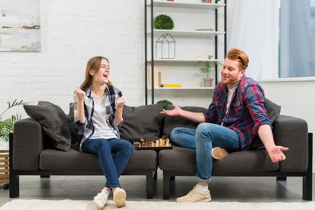 Junge frau, die ihre faust mit der freude zusammenpreßt, die seinen zuckenden freund beim spielen des schachs betrachtet