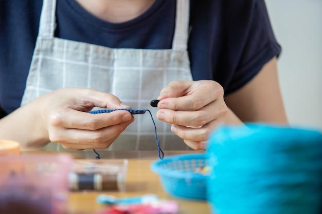 Junge frau, die ihre freizeit mit dem handwerklichen hobby verbringt. geschickte frau, die einen häkelhut und eine tasche während des aufenthalts zu hause macht. das arbeitskonzept inspiration und kreativität mit kopierraum.