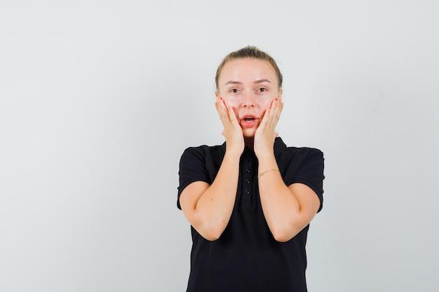 Junge frau, die ihre hände auf wange mit offenem mund im schwarzen t-shirt hält und überrascht aussieht