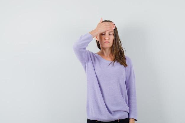 Junge frau, die ihre hand auf stirn in lila bluse hält und stressig aussieht. vorderansicht.