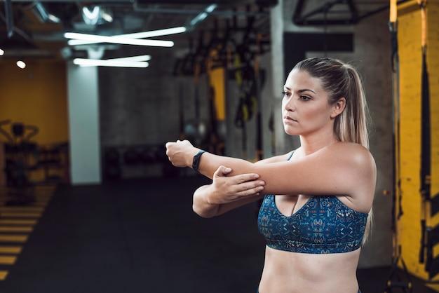 Junge frau, die ihre hand im fitnessclub ausdehnt