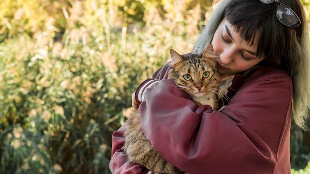 Junge frau, die ihre katze der getigerten katze im garten umarmt
