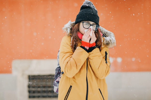 Junge frau, die ihre nase mit einem gewebe im freien im winter durchbrennt. junge frau, die mit grippe an einem wintertag krank wird