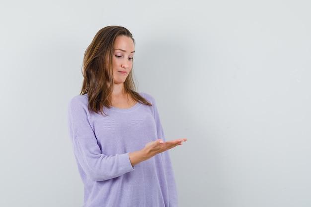 Junge frau, die ihre offene handfläche in der lila bluse betrachtet und konzentriert schaut