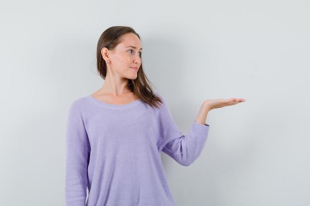 Junge frau, die ihre offene handfläche in lila bluse beiseite spreizt und froh aussieht