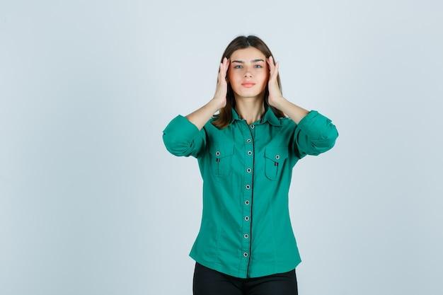 Junge frau, die ihre schläfen im grünen hemd reibt und entspannt aussieht. vorderansicht.
