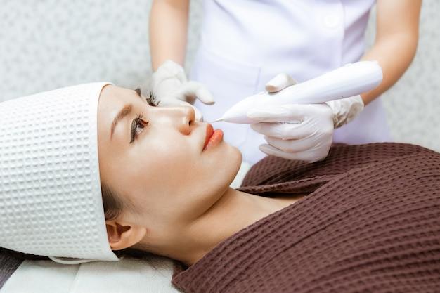 Junge frau, die ihre schönheitsbehandlung von einem doktor an einer schönheitsklinik erhält