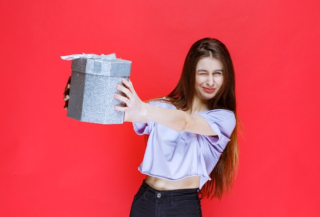 Junge frau, die ihrem freund eine silberne geschenkbox anbietet.