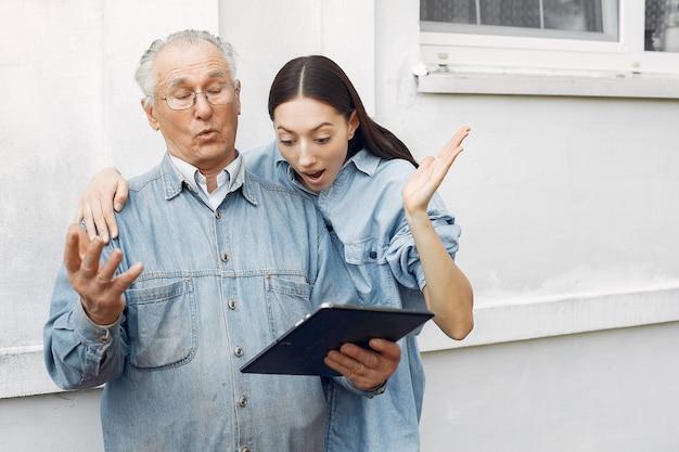 Junge frau, die ihrem großvater beibringt, wie man eine tablette benutzt