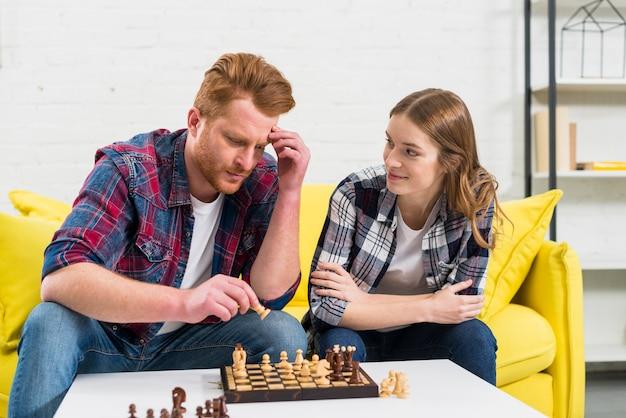 Junge frau, die ihren durchdachten freund spielt das schach betrachtet