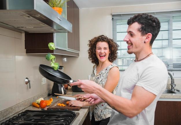 Junge frau, die ihren ehemann wirft brokkoli in der bratpfanne betrachtet