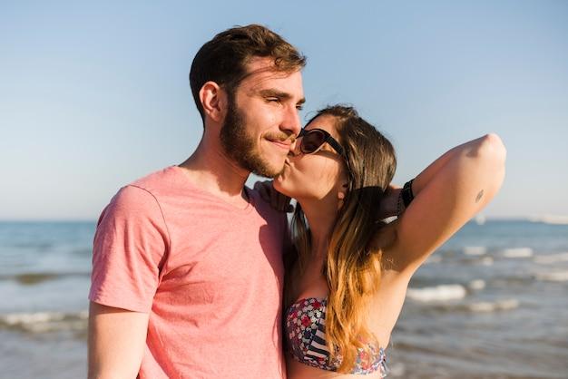 Junge frau, die ihren freund am strand küsst