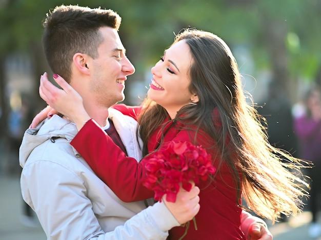 Junge frau, die ihren freund umarmt, weil er ihr blumen gab - valentinstagkonzept