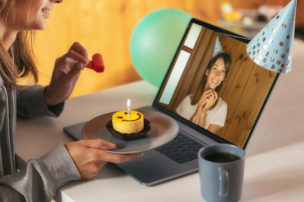 Junge frau, die ihren geburtstag zu hause mit freunden auf videoanruf feiert