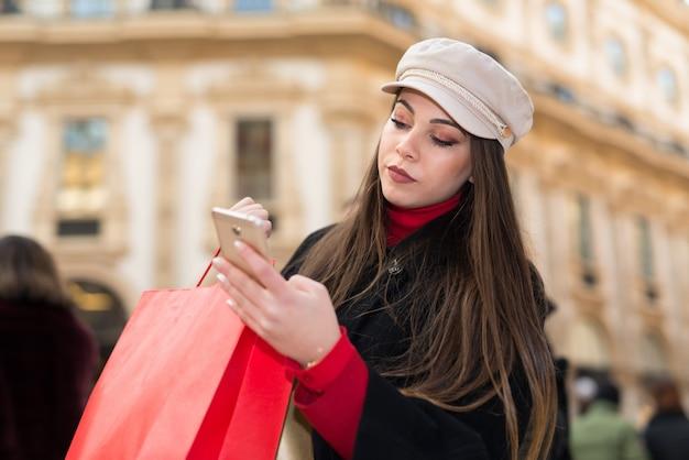 Junge frau, die ihren handy in der stadt beim tragen von einkaufstaschen verwendet