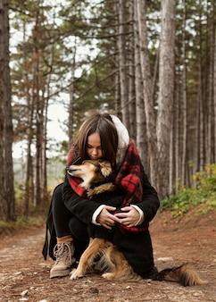 Junge frau, die ihren hund im wald umarmt