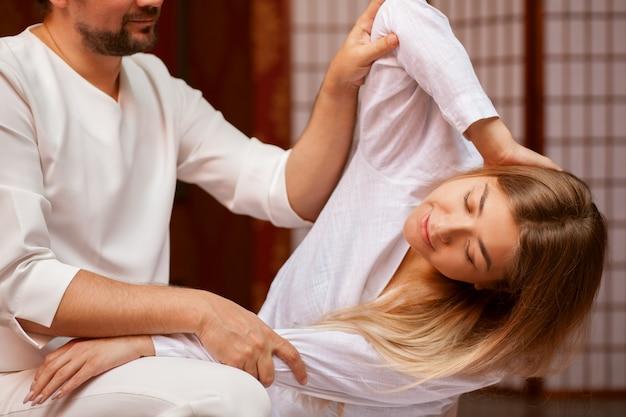 Junge frau, die ihren körper mithilfe des professionellen thailändischen massagetherapeuten in der badekurortmitte ausdehnt. männlicher masseur, der thailändische massage an seinem kunden durchführt. erholung, entspannung, heilung