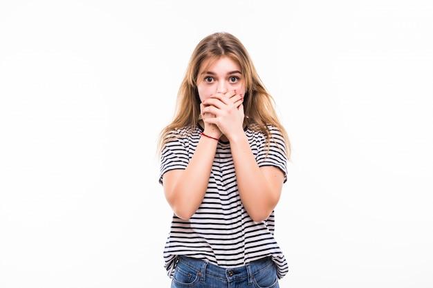 Junge frau, die ihren mund bedeckt, lokalisiert auf weißer wand