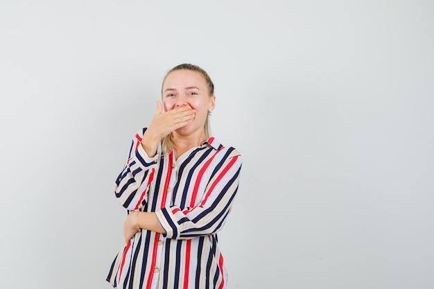Junge frau, die ihren mund mit einer hand in gestreifter bluse bedeckt und überrascht aussieht