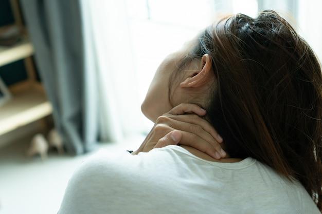 Junge frau, die ihren nacken im schmerz hält. medizinisches konzept