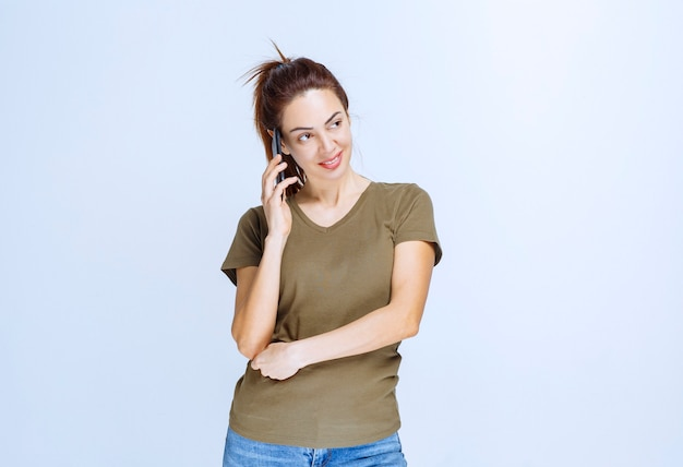 Junge frau, die ihren partner anruft und mit dem telefon spricht