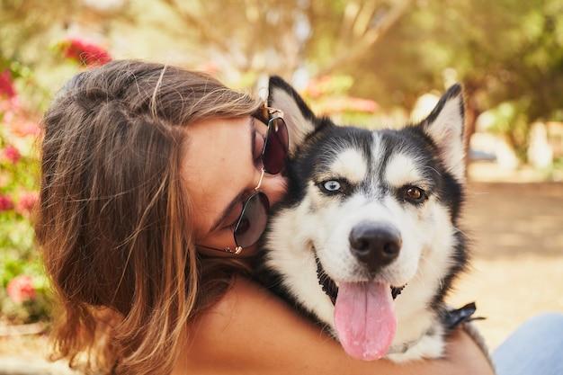 Junge frau, die ihren sibirischen husky im park küsst