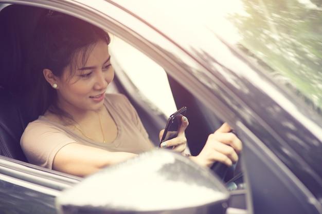Junge frau, die ihren smartphone beim autofahren an einem sonnigen tag mit sonnenlicht betrachtet