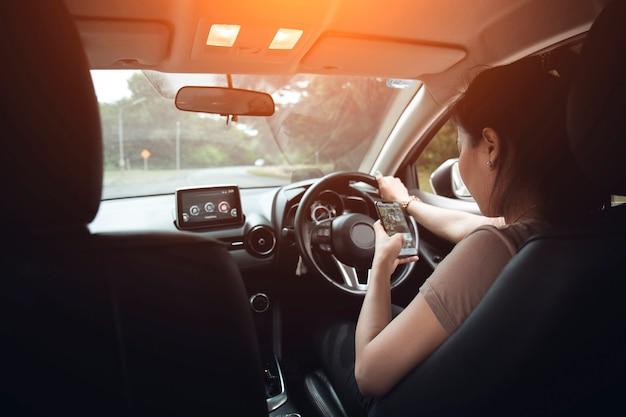 Junge frau, die ihren smartphone beim autofahren betrachtet