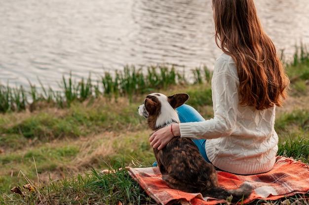 Junge frau, die ihren walisischen corgi-hund nahe fluss im freien umarmt