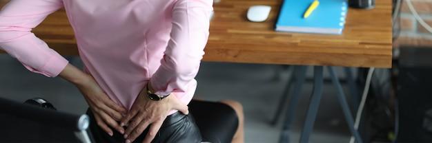 Junge frau, die ihren wunden unteren rücken mit den händen am arbeitsplatz am tisch in der bürogesundheit hält