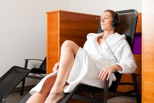 Junge frau, die im badekurort mit musik sich entspannt