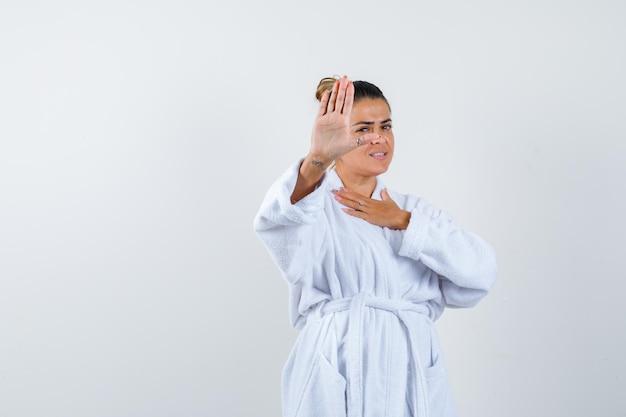 Junge frau, die im bademantel eine stopp-geste zeigt und selbstbewusst aussieht