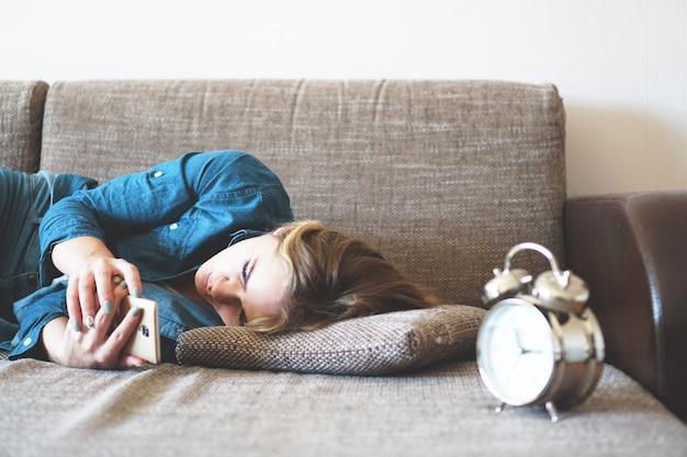 Junge frau, die im bett telefoniert, auf den bildschirm schaut, schlaflosigkeit, zeit überprüfen, mit smartphone aufwachen, handysucht - wecker in der nähe