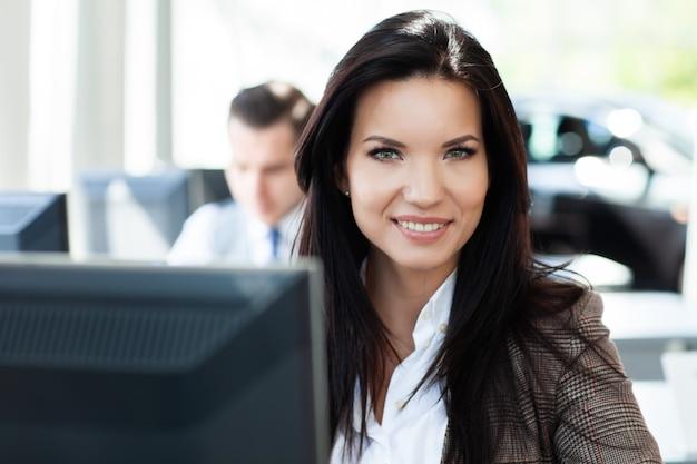 Junge frau, die im büro arbeitet, am schreibtisch sitzt, mit laptop.
