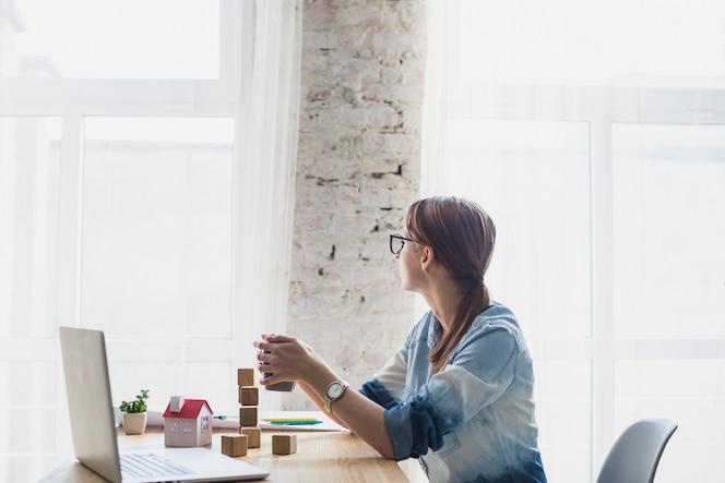 Junge frau, die im büro hält kaffeetasse in der hand sitzt