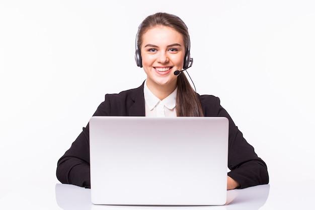 Junge frau, die im büro mit laptop und kopfhörern auf weißer wand, kundendienst und callcenter arbeitet.