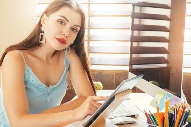 Junge frau, die im büro unter verwendung des computers, sitzend am schreibtisch arbeitet