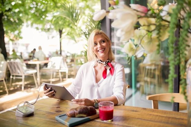 Junge frau, die im café unter verwendung der digitalen tablette sitzt