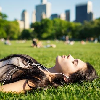 Junge frau, die im central park legt auf das gras und hört musik sich entspannt. new york city.