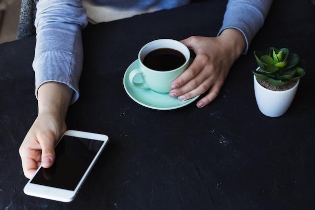 Junge frau, die im diner mit tasse kaffee sitzt