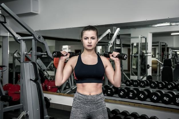 Junge frau, die im fitnessstudio an der sportausrüstung trainiert