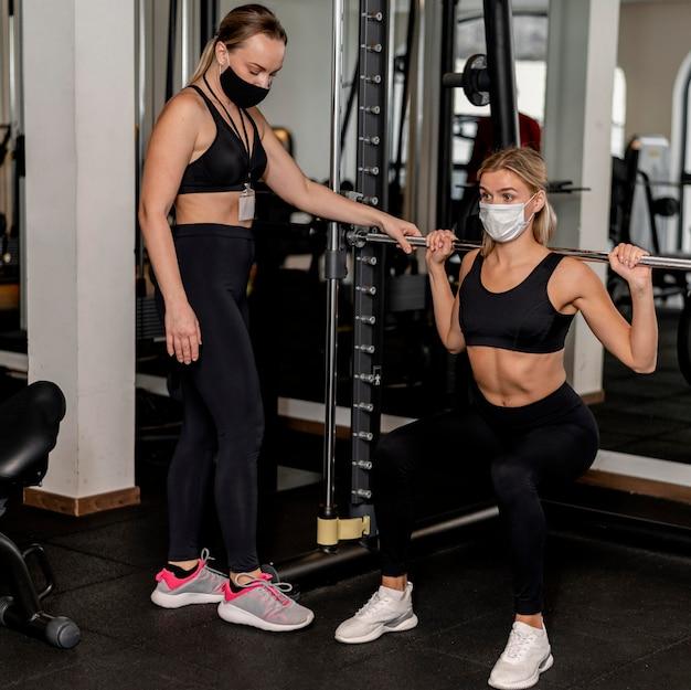 Junge frau, die im fitnessstudio und ihre trainerin trainiert