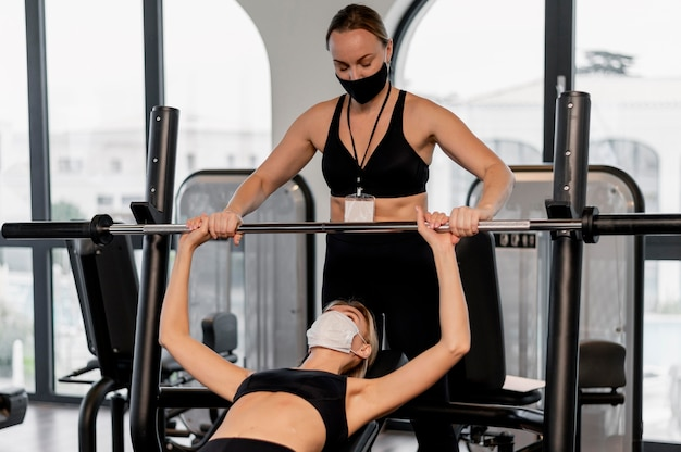 Junge frau, die im fitnessstudio und in ihrem trainer trainiert