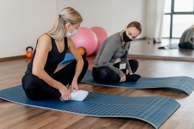 Junge frau, die im fitnessstudio und trainer auf yogamatten trainiert