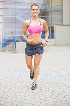 Junge frau, die im freien joggt oder läuft. joggen ist zu meinem alltag geworden