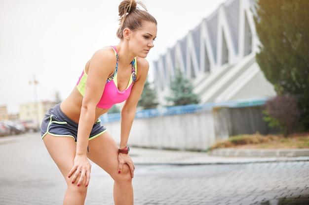 Junge frau, die im freien joggt oder läuft. manchmal braucht man eine längere pause, um zu atmen