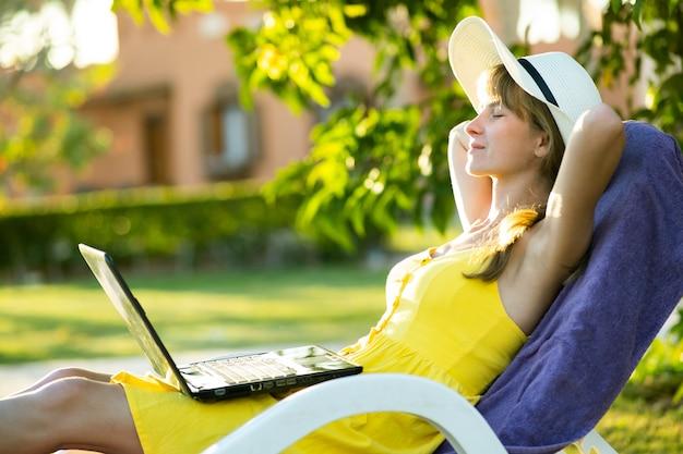 Junge frau, die im grünen garten auf einem stuhl nach der arbeit auf laptop verbunden mit drahtlosem internet im sommerpark ruht. während der quarantäne im urlaubskonzept geschäfte machen und aus der ferne studieren.
