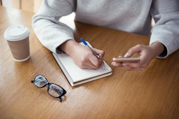 Junge frau, die im kreativen stilvollen büro sitzt, das s hält